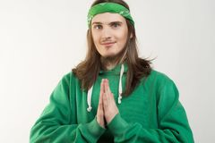 Portrait of young handsome smiling happy man in green hoodie looking at the camera and showing namaste agains white background. Royalty Free Stock Photos