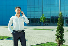 Portrait of young handsome successful business man. Portrait of young handsome successful business man near blue wall of business centre speaking over mobile Stock Image