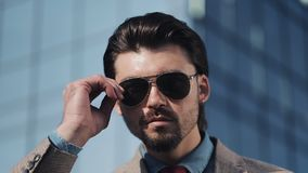 Portrait of Young Handsome Successfull Bussinessman in a Suit Wear Sunglasses Standing near modern Office Centre Close stock video