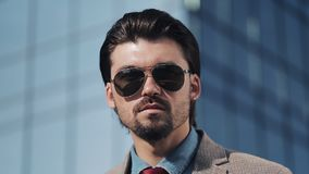 Portrait of Young Handsome Successfull Bussinessman Wearing a Suit and Sunglasses Standing near modern Office Centre stock video footage