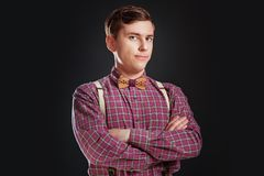 Portrait of young handsome suspicous man in vintage shirt and bow tie with hairstyle keeping hands cross while standing on black. Background. Doubt Emotion Stock Images