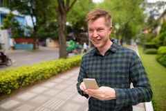 Young handsome tourist man using mobile phone in Vietnam. Portrait of young handsome tourist man exploring Ho Chi Minh city in Vietnam stock images