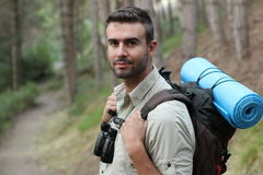 Portrait of a young handsome wanderer man with backpack goes down the road with copy space, happy hiker walking lonely in mountain Royalty Free Stock Photography