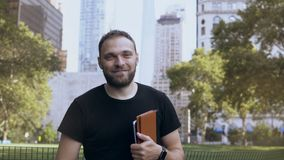 Portrait of young handsome worker male, holding the documents near the financial district in New York, America. Attractive businessman smiling at camera stock video footage