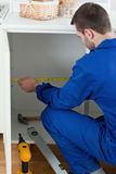 Portrait of a young handyman measuring something Royalty Free Stock Photo