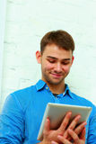Portrait of a young hapiness businessman holding tablet computer. And looking at it Royalty Free Stock Photography