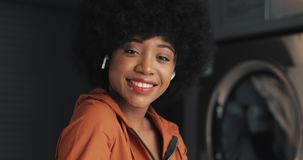 Portrait of young happy African American woman wearing earphones looking into the camera. Self-service public laundry. Background. Close-up stock video footage