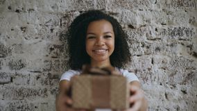 Portrait of Young happy african girl present gift box and smiling into camera. Young happy mixed race girl present gift box and smiling into camera Royalty Free Stock Photo