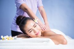 Happy woman relax in spa. Portrait of young happy Asian beautiful woman relax in spa. Body care treatment. Cute girl having massage at back by professional Royalty Free Stock Images