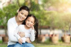 Portrait of young happy asian mother and little cute daughter smiling, sitting and looking at camera at outdoor public nature park royalty free stock photos