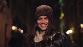 Portrait of Young Happy Attractive Girl in Winter Hat and Mittens Walking in Falling Snow, Pointing and Smiling to