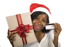Portrait of young happy and beautiful black African American woman in Santa Claus hat holding present box and credit card in Chris royalty free stock photos