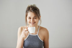 Portrait of young happy beautiful girl smiling looking at camera holding drinking cup of coffee at morning over white. Wall. Copy space Royalty Free Stock Image