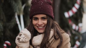 Portrait of Young Happy Beautiful Girl in Winter Clothes Standing in Falling Snowflakes Outside, Smiling, Dancing at. Christmas Decorated Window Shop Background stock video