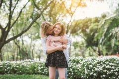 Mother and Daughter Hugging. Portrait of Young Happy Beautiful Mother and Daughter Hugging. Embrace in Sunny Day on Meadow Stock Photos