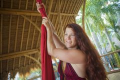 Portrait of young happy and beautiful red hair woman at aerial dancing workshop learning aero dance holding silk fabric smiling. Cheerful in tropical wooden hut royalty free stock photo