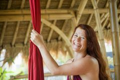 Portrait of young happy and beautiful red hair woman at aerial dancing workshop learning aero dance holding silk fabric smiling. Cheerful in tropical wooden hut stock photo