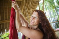 Portrait of young happy and beautiful red hair woman at aerial dancing workshop learning aero dance holding silk fabric smiling. Cheerful in tropical wooden hut stock photos