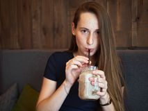 Portrait young happy beautiful redhead woman with freckles drinking coffee in cafe at coffee break. Portrait young happy beautiful redhead lady with freckles Royalty Free Stock Images
