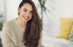 Portrait of a young happy beautiful woman in warm clothings at home stock photography