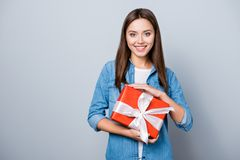 Portrait of young, happy birthday girl, holding a present in red. Packaging with bow, standing over grey background Stock Photography