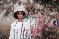 Brazilian toursit girl in hat outdoors surrounded by native grasses. Portrait of a young happy black tourist female in the hat and chemise standing on the summer stock photography