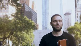 Portrait of young happy businessman standing in the park, near the offices and skyscrapers in New York, America. Portrait of young happy businessman standing in stock video