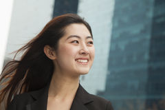 Portrait of young happy businesswoman outdoors among skyscrapers Stock Photos