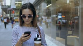 Portrait of young happy businesswoman standing with coffee cup near the office building and using the smartphone. Busy female typing message on mobile phone stock video