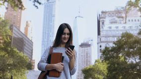 Portrait of young happy businesswoman standing near the office building, holds notebooks and use the smartphone. Female manager working in Internet from device stock video