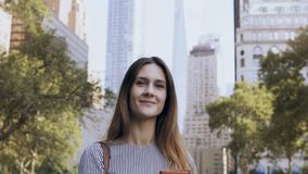 Portrait of young happy businesswoman standing in the park of financial centre of New York, USA and holding documents stock video footage