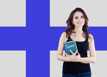 Portrait of young happy cheerful woman with book on the Finnish flag. Beautiful girl learning finnish language royalty free stock photography