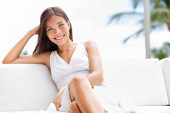 Portrait of young happy confident asian woman. Sitting outside in sofa smiling at camera with professional self assured confidence. Beautiful multicultural Stock Image