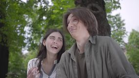 Portrait young happy couple in casual clothes spending time together in the park, having a date. Lovers sitting on the stock footage