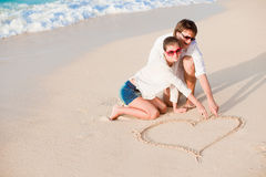 Portrait of young happy couple drawing a heart on. The sand. This image has attached release Royalty Free Stock Photo