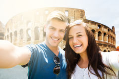 Portrait Of A Young Happy Couple. In Front Of Coliseum Royalty Free Stock Images
