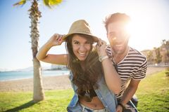 Young happy couple laughing outside in sunlight. Portrait of young happy couple laughing outside in sunlight Royalty Free Stock Images