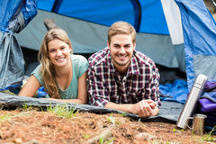 Portrait of a young happy couple lying in a tent Stock Images