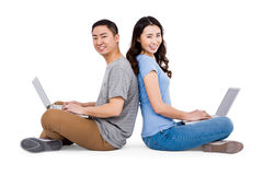 Portrait of young happy couple using laptop while sitting Royalty Free Stock Images