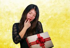 Portrait of young happy and excited beautiful Asian Chinese woman receiving a romantic anniversary gift box holding the. Red ribbon present cheerful for stock image