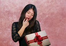 Portrait of young happy and excited beautiful Asian Korean woman receiving a romantic anniversary gift box holding the r. Ed ribbon present cheerful for birthday royalty free stock images