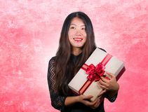 Portrait of young happy and excited beautiful Asian Korean woman receiving a romantic anniversary gift box holding the r. Ed ribbon present cheerful for birthday stock image