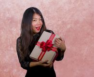 Portrait of young happy and excited beautiful Asian Korean woman receiving a romantic anniversary gift box holding the r. Ed ribbon present cheerful for birthday stock images