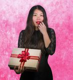 Portrait of young happy and excited beautiful Asian Korean woman receiving a romantic anniversary gift box holding the r. Ed ribbon present cheerful for birthday stock photo
