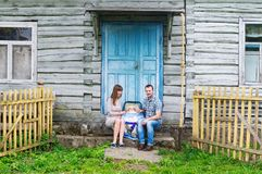 Portrait of young happy family with baby kid in baby carriage sitting together in front of old retro wooden house stock photo