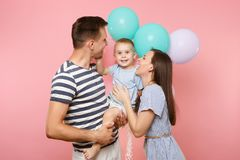 Portrait of young happy family, parents keep in arms, kissing hugging child kid son baby boy, celebrating birthday stock photo