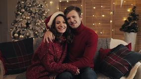Portrait of young happy family sitting on the sofa near Christmas tree at home. Couple celebrating New Year looking at. The camera. Christmas Couple stock video footage