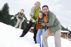 Portrait of young happy family standing in snow Stock Images