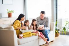 Young family with two children and tablet preparing for holidays. Royalty Free Stock Image