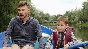 Portrait of young happy father and little son on wooden boat in park. Father and little child resting in park on boat and smiling. Happy father and son float stock footage